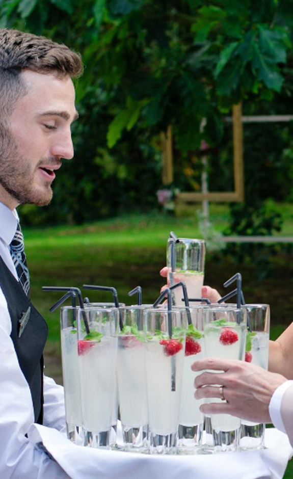 A Waiter from Tipples Mobile Bars and Catering Hire carrying a tray of drinks.