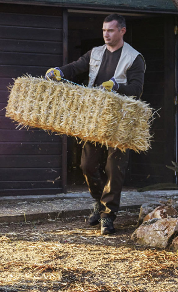 A Farmer carrying a bale of straw